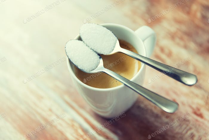 close up of white sugar on teaspoon and coffee cup