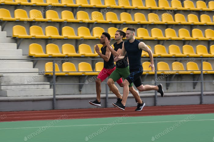 Multiethnic athlete group run on running track outdoors