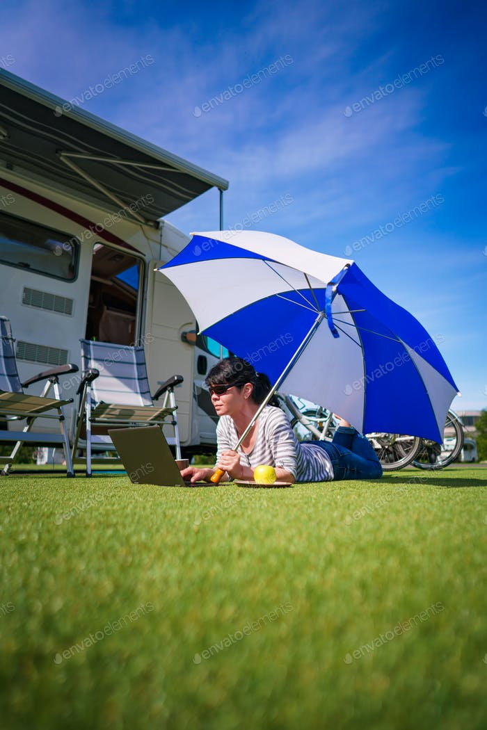 Woman on the grass, looking at the laptop under umbrella near th