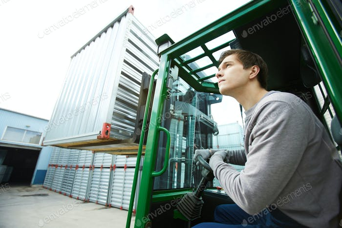 Serious man operating forklift
