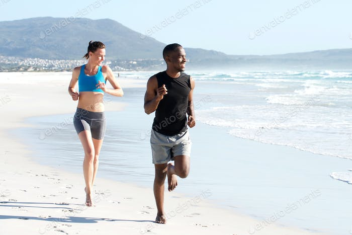 Healthy active couple running by water on the beach
