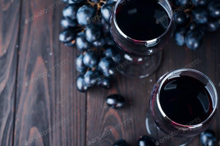 Rotwein in Gläsern mit Traube