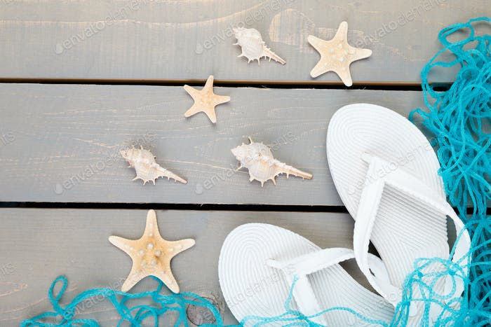 Seashells and white flip flops grey wooden background. Flat lay.