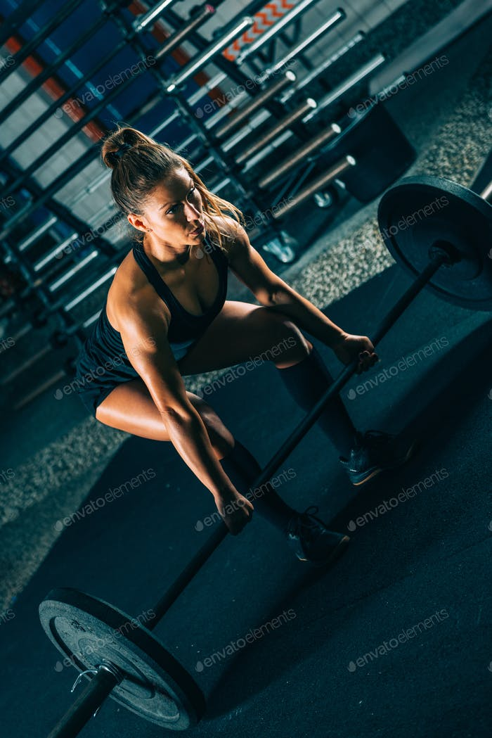 Cross training. Female athlete lifting heavy barbells