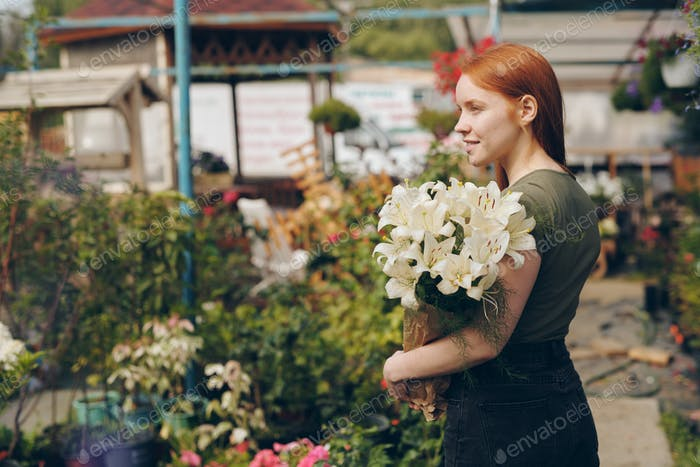 Smiling beautiful redhead girl holding lilies in paper bag