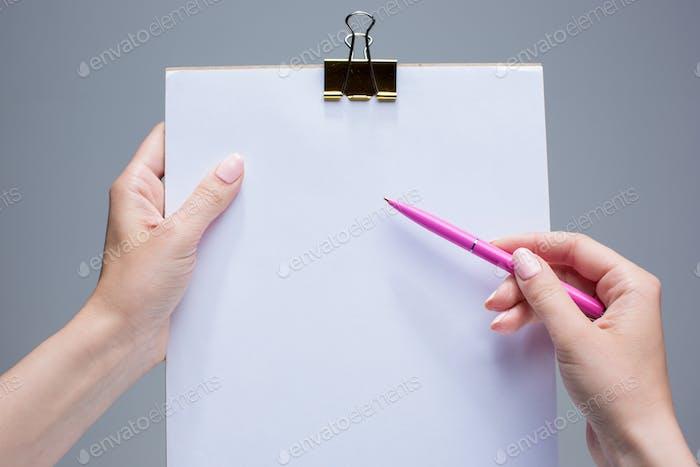 El bloc de notas y la pluma en manos Mujer