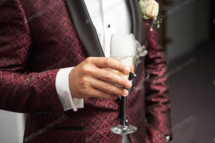 Close up of man holding a glass of champagne in hand