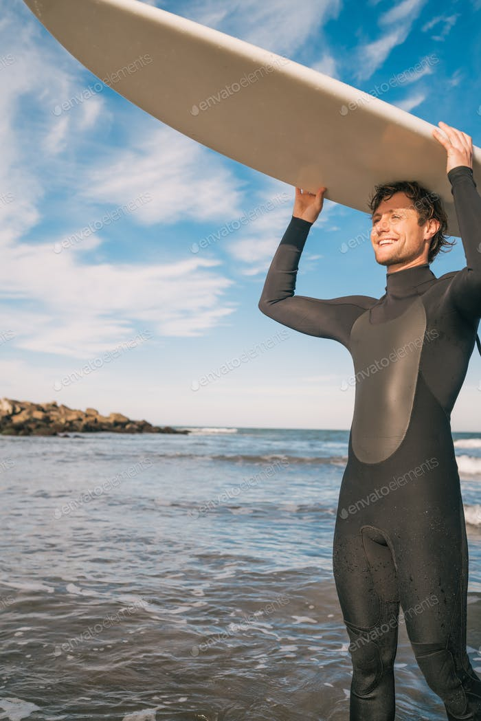 Young surfer holding up his surfboard.