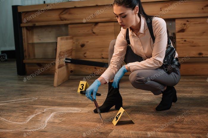 detective concentrada recolectando pruebas en la escena del crimen