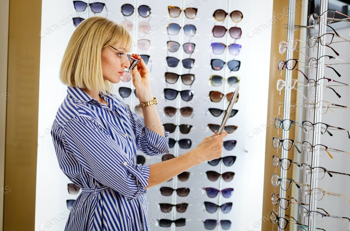 Beautiful young woman choosing new pair of spectacles in opticians store. Optics. Ophthalmology