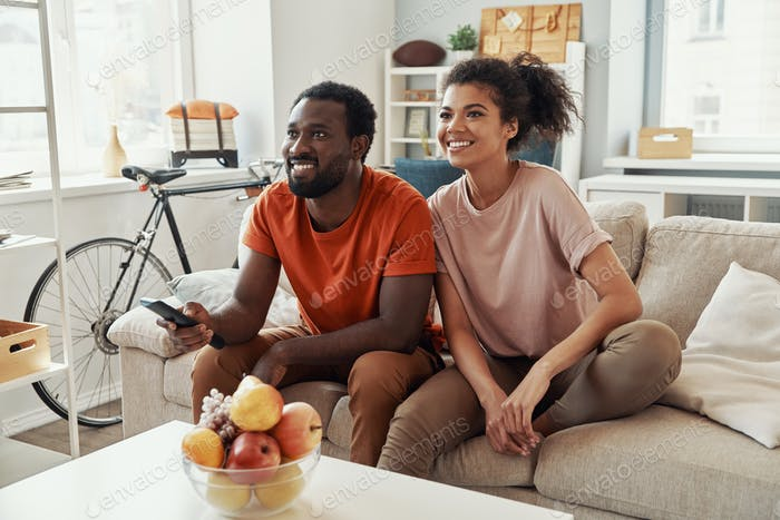 Beautiful young African couple watching TV and smiling while spending time at home
