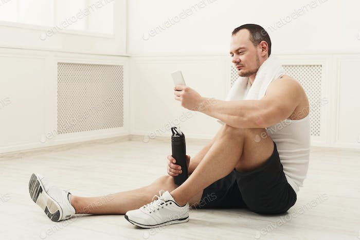Male bodybuilder drinking water after workout