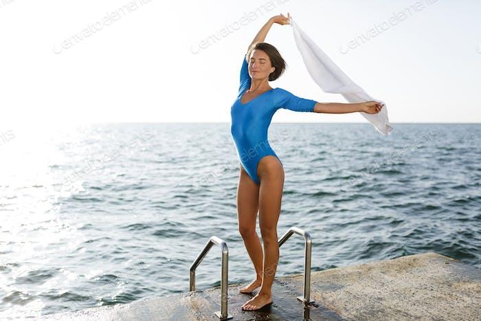 Niedliche Frau in blau Badeanzug stehend und halten weißes Handtuch während heben ihre Hände hoch