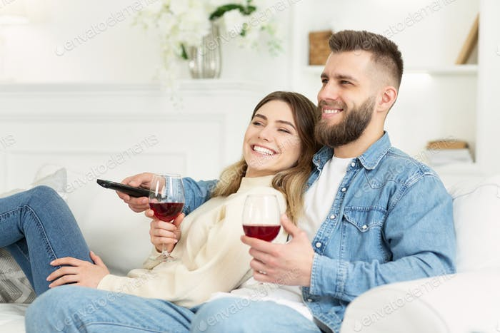 Loving couple drinking wine and watching tv, enjoying evening