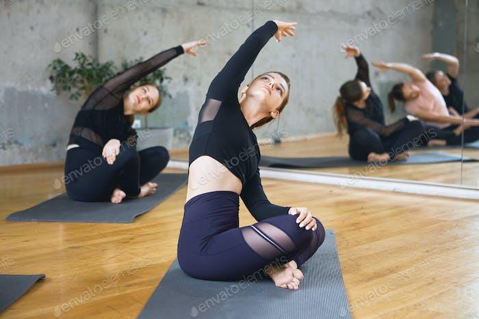 Women practicing stretching in lotus pose on mats