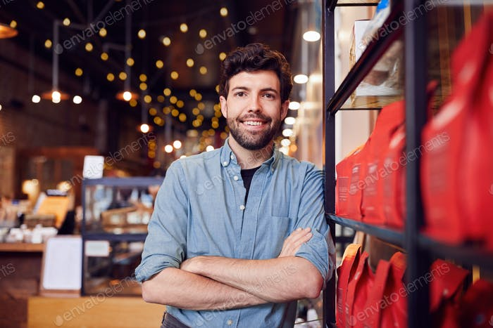 Portrait Of Male Coffee Shop Owner Standing By Counter