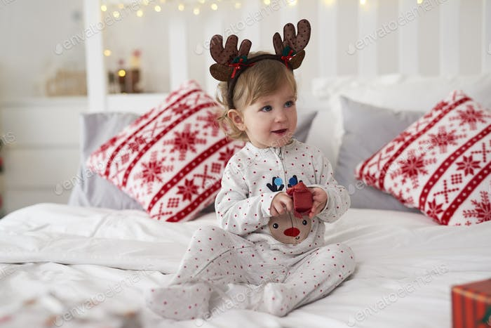 Charming baby opening the Christmas present in bed