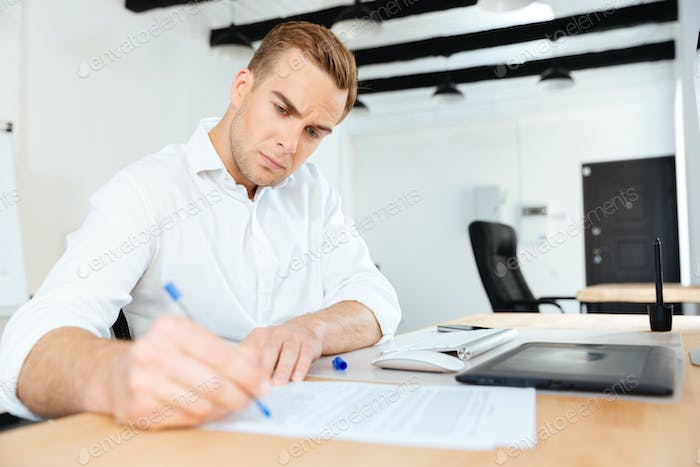 Businessman sitting in office and writing