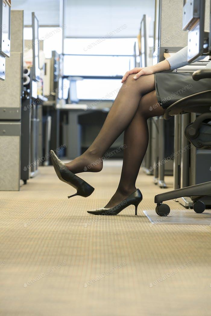 Eine Nahaufnahme von Beinen, Rock und Schuhen einer Geschäftsfrau in einem Unternehmens- büro.