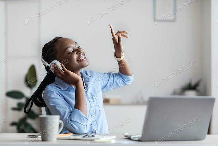 Life Is Good. Cheerful Black Female Entrepreneur Listening Music At Workplace