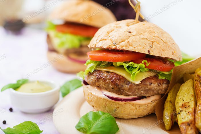 Big sandwich - hamburger with juicy beef burger, cheese, tomato, and red onion