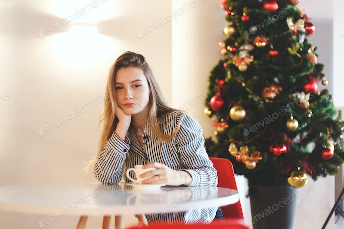 Young beautiful woman drinks hot coffee in cafe with Christmas tree decorations