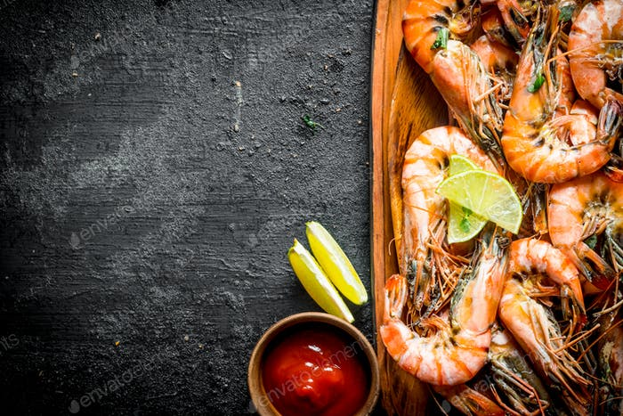 Fried shrimps on a plate with sauce and lime.
