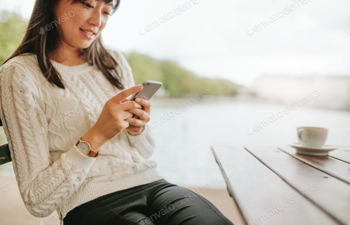 Attractive young female using cellphone at cafe