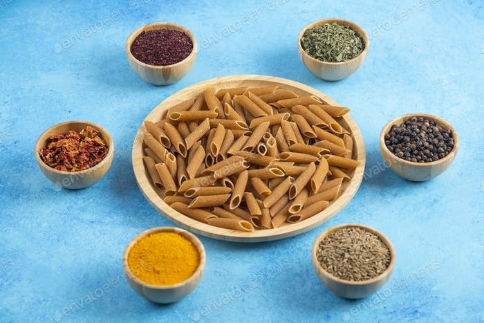 Various kinds of spices around brown pasta