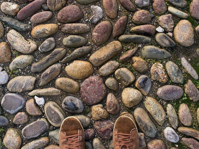 Feet in brown sneakers on the old medieval stone pavement.
