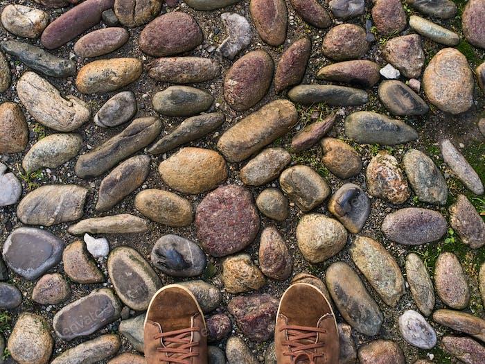 Füße in braunen Sneakers auf dem alten mittelalterlichen Steinpflaster.