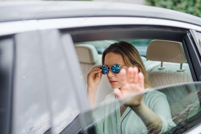 Junge Frau mit Sonnenbrille sitzt auf dem Rücksitz des Autos, versteckt vor Paparazzi