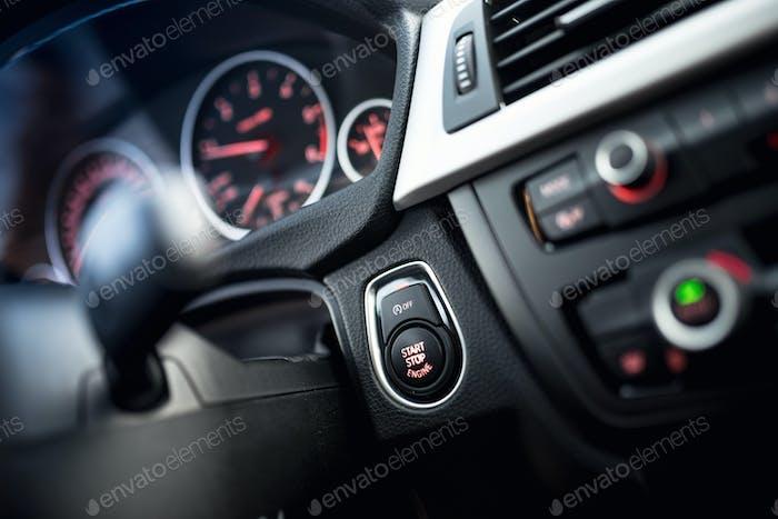 Nahaufnahme der Autostart- und Stopp-Taste. Moderner Innenraum mit Armaturenbrett und Cockpitdetails
