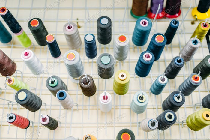 Colorful threads on spools closeup, side view