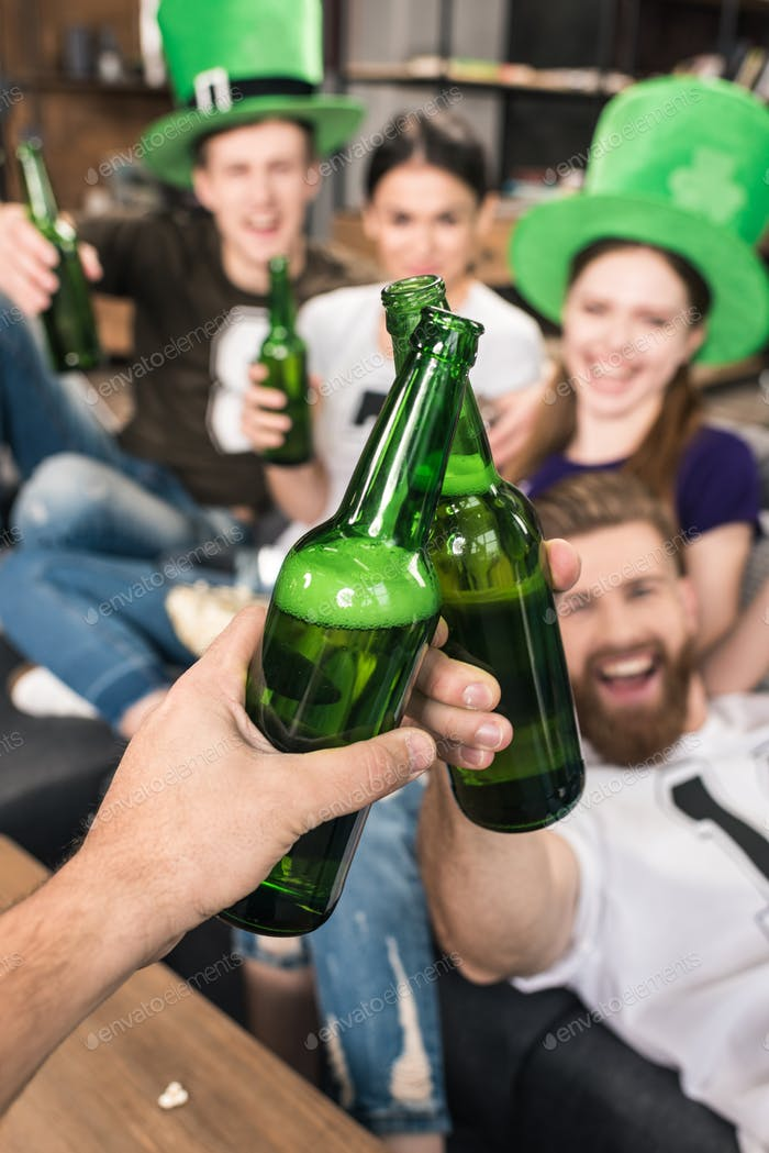 Close-up view of friends clinking beer bottles, st patricks day concept