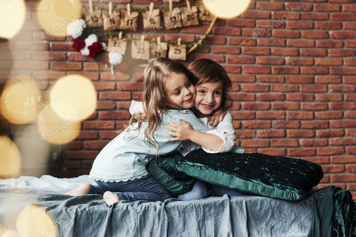 True friendship. Little girls having fun on the bed with holiday interior at the background