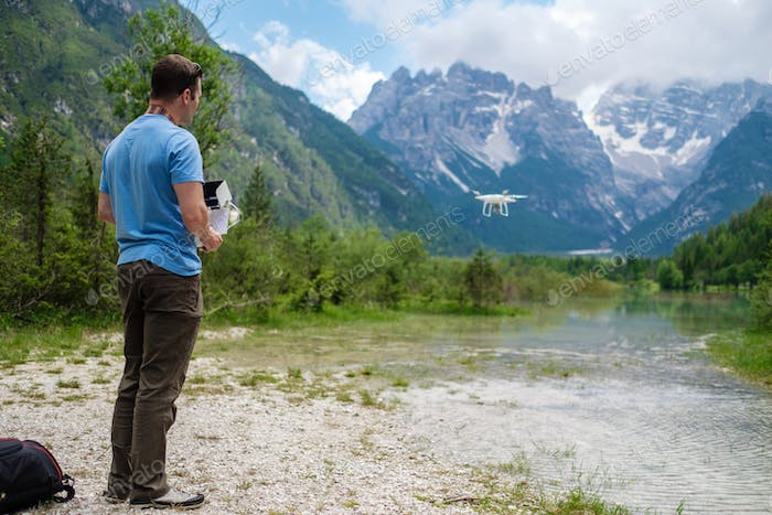 Man controls drone with mountains on background. Alps, Italy.