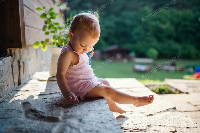 A cute toddler girl sitting outdoors in front of house in summer.