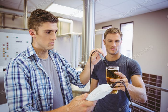Two casual men testing beer in the beaker in the factory
