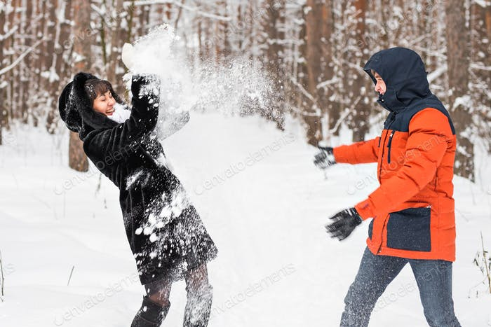 Young couple playing in snow, having snowball fight
