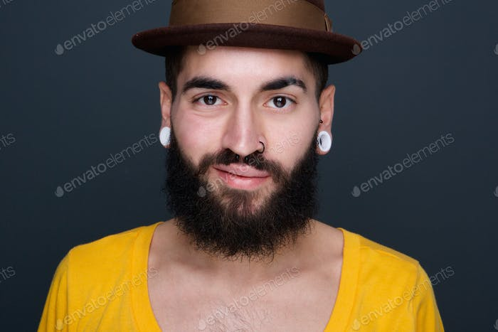 Trendy young man with beard and piercings