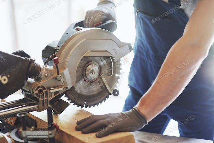 young handsome carpenter working behind a circular saw in the workshop