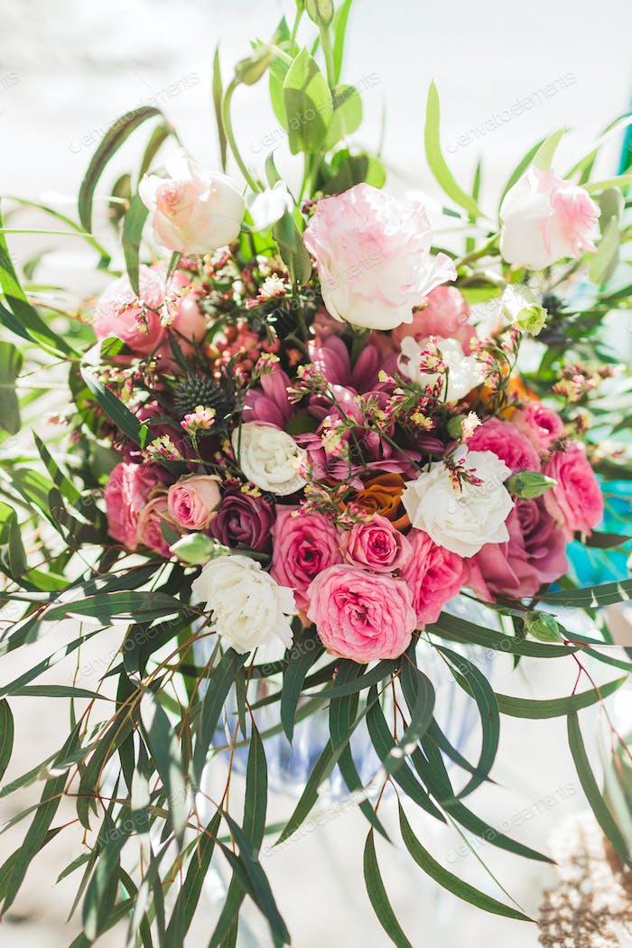 Hochzeitsstrauß im Boho-Stil mit rosa Seidenbändern, Rosen, Chrysanthemen und tropischen Pflanzen