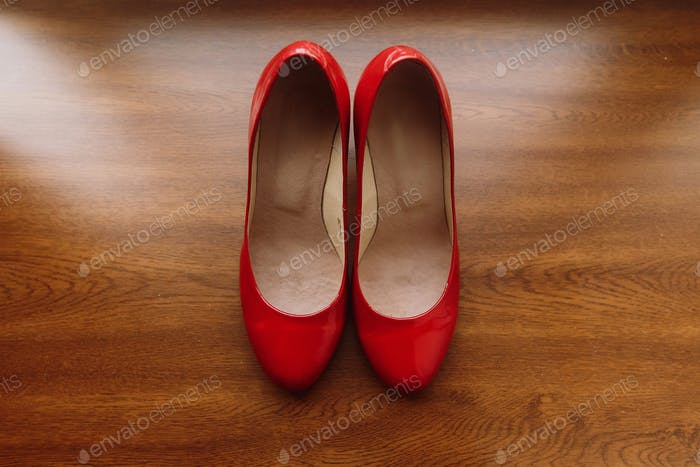 Stylish red women's shoes on wooden floor, elegant bride's shoes closeup on rustic background