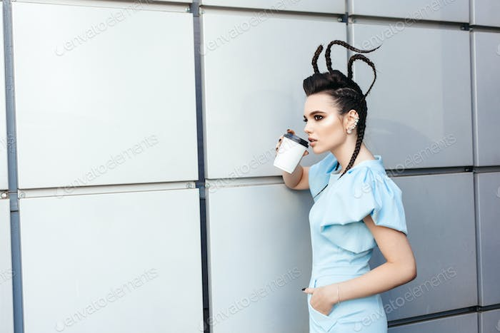 woman showing hot drink in disposable paper cup