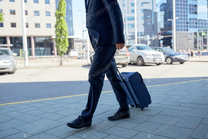 senior businessman walking with travel bag in city