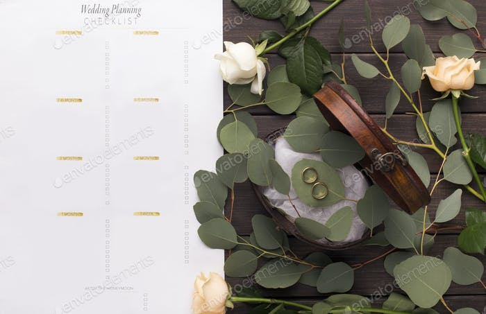 Wedding rings and paper planning checklist on wooden table