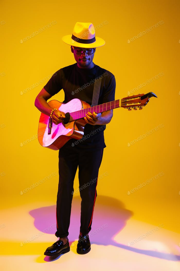 Young african-american musician singing, playing guitar in neon light