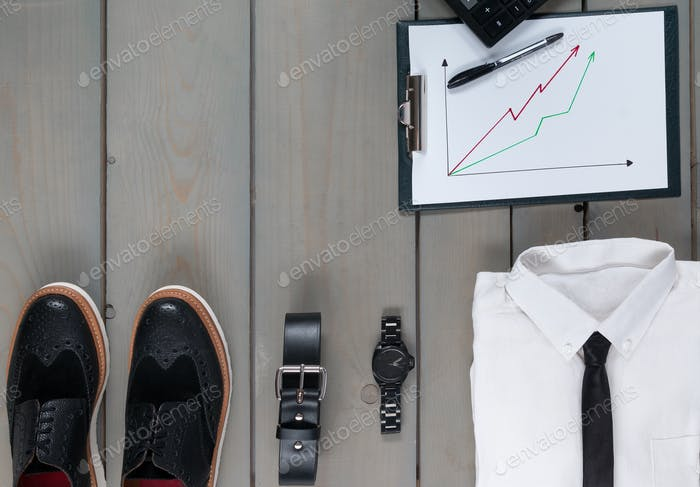 Businessman, work outfit on grey wooden background.