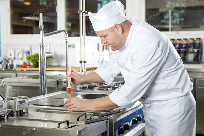 Chef using brush to prepare a dish in the kitchen